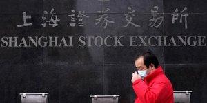 Coronavirus : un homme portant un masque devant le bâtiment du Shanghai Stock Exchange