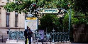 Deux personnes lisent le plan du métro parisien à la station Cité (Paris, tourisme, Île-de-France, vélos à Paris, transport en commun, transport parisien)