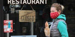 Fermeture commerce restaurant. Une femme portant un masque et une baguette passe devant un restaurant fermé à cause de l'épidémie de coronavirus, le 16 avril 2020 à Cannes