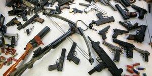 Un arsenal d'armes à feu (pistolets, munitions, fusils) posé sur une table à Manchester